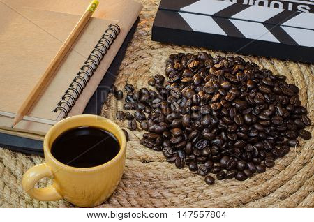 Cup of coffee with notebook slate on a jute rope.