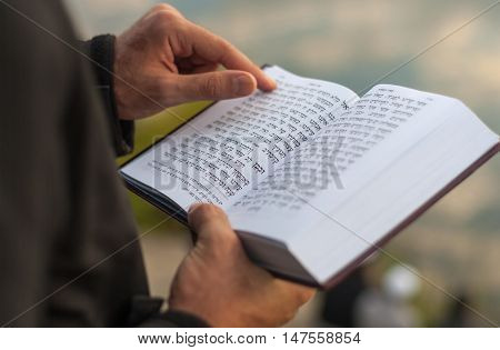 UMAN, UKRAINE SEPTEMBER 15, 2015: Man holding Mahzor - prayer book used by Jews on the High Holidays of Rosh Hashanah and Yom Kippur. Religious book Mahzor. Rosh Hashanah.