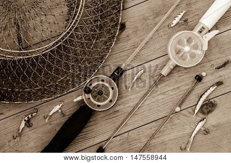 Fishing accessories for winter. Tackles bait lure jig hook net. Wooden background. Outdoor activity and leisure concept. Toned.