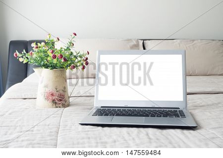 The bed with blank screen on laptop and mushroom flower on flower pot View from Notebook screen.