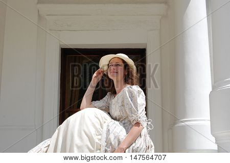 European woman sitting in sunshine and touching hat in vintage dress near palace. White color, curly hair, sensitive, sensuality.