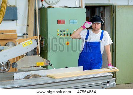 Worker In Workshop Using Saw Machine