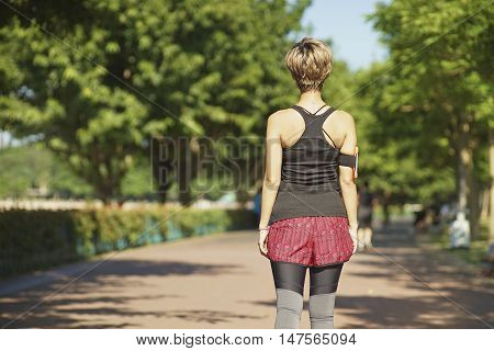 young Chinese woman walking after jogging in summer