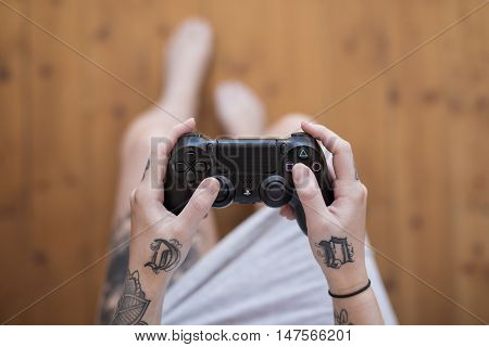 Gothenburg, Sweden - September 17, 2016: A close up shot from above of a tattooed young woman's hands holding a black video game controller for the Playstation 4, developed by Sony.