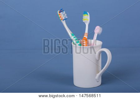 Toothbrushes in a cup on a blue wooden table