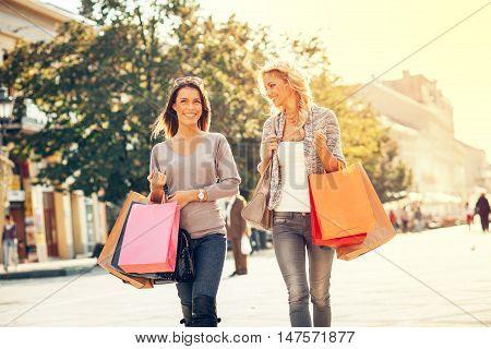 Two beautiful women walking down the street after shopping