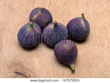 Still-life with five ripe figs fruits on brown wooden surface horizontal view closeup