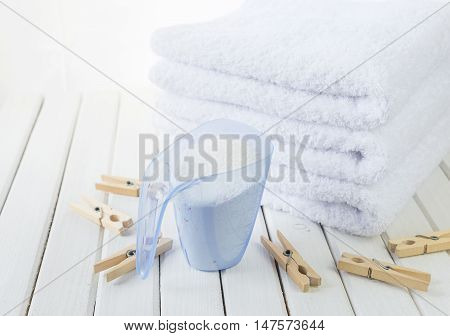 Stack of three white fluffy bath towels washing powder in measuring cup and wooden clothespins on the background of white boards