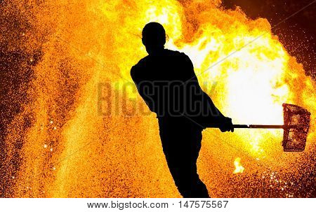 Fireshow performance. Silhouette of man with hammer, fire around