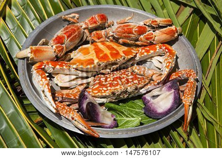 Dish with cooked crabs on the background of palm leaf