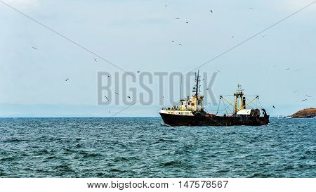 SOZOPOL, BULGARIA - JULY 24, 2016: Cutter returns from fishery in Sozopol, one of the oldest Bulgarian towns founded in the 7th century BC, nowadays one of the major seaside resorts in the country.