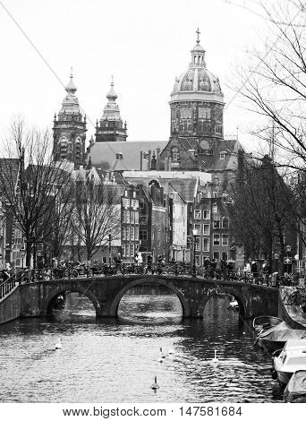 The Oudezijds Voorburgwal a street and canal in the Red-light district in the center of Amsterdam. In the background Basilica of St. Nicholas. Black and white