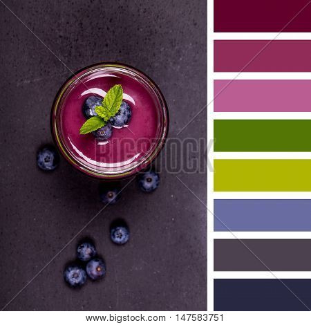 A blueberry smoothie with a sprig of mint and surrounded by fresh blueberries, in a glass jar with a straw and over a chalkboard background. In a colour palette with complimentary colour swatches.