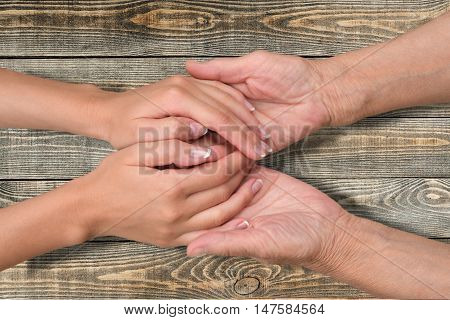 man and woman holding hands on wooden table. Couple holding hands. Consoling hands.