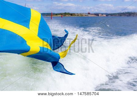 Swedish flag (ensign) waving from the back of a boat