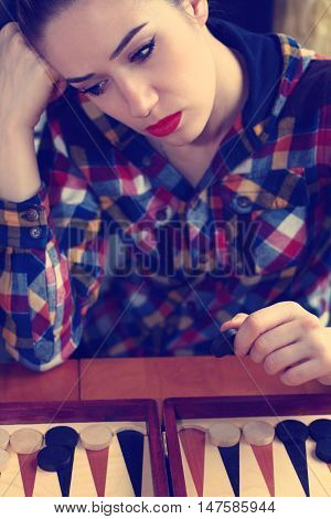 Young girl playing backgammon in the room.