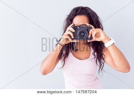 Real photographer. Pleasant young woman holding photo camera and making photos while standing isolated on grey background