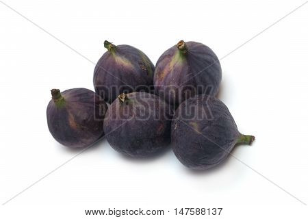 Indoor still-life with five ripe figs fruits isolated on white background top view closeup