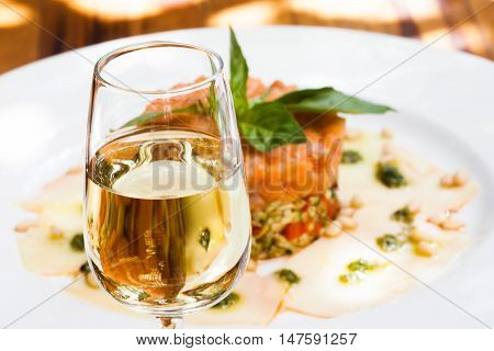 Glass of sherry jerez, pink salmon fish tartar plate background, soft focus photo