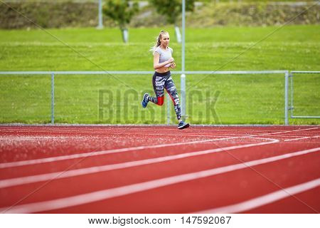 Full length of determined young woman running on sports tracks
