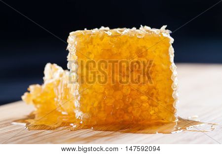 Natural honeycomb on the wooden board and dark background. Organic yellow, gold honeycomb texture with fresh honey. selective focus