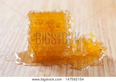 Organic honeycomb on the wooden board and pastel background. Tasty yellow, gold honey combs texture with fresh honey.