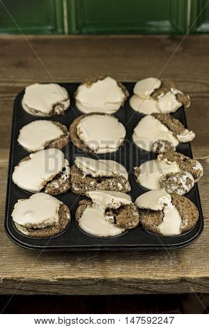 One dozen freshly baked muffins with brown frosting inside muffin tin on wooden table