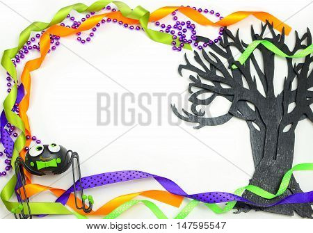 Halloween border of a rough textured wooden cutout of bare tree shape painted black. A silly spider and purple green and orange ribbons and beads frame the copy space on white background