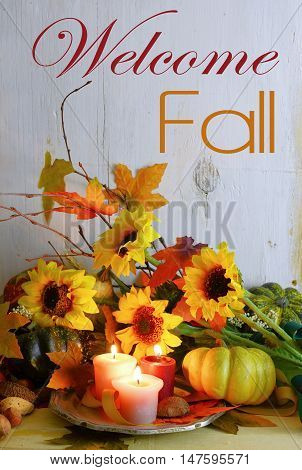Fall still life with gourds candles autumn leaves twigs and sunflowers on a rustic wooden background with a vintage filter applied. Vertical orientation with message added