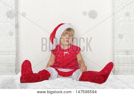 Little girl in Santa suit sitting on floor with snow studio shot