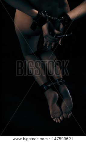 Low key photo of sexy female nude legs binded with cuffs holding whip against dark background