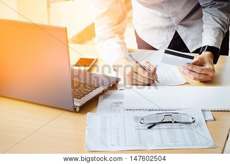 Business man's hands holding a credit card Writing payment document and using laptop for online shopping vintage tone