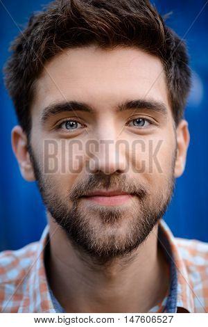 Close up portrait of young handsome man smiling, looking at camera over blue background.