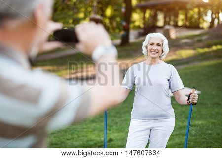 Achieved Husband takes a photo of his attractive elder wife after doing sports in park