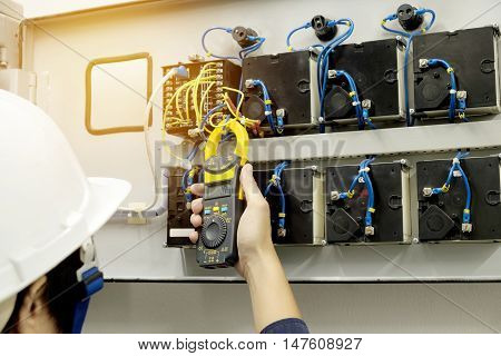 Technician is measuring voltage or current by Clampmeter
