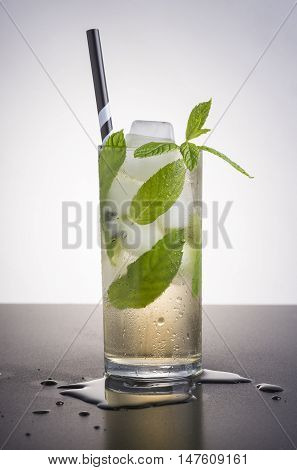 A refreshing cocktail with ice, mint leaves and a striped straw.