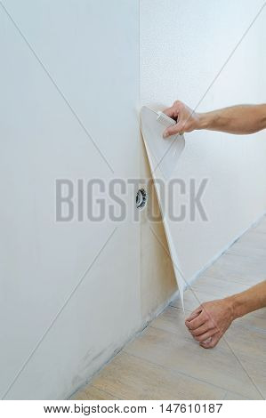 Worker pasting wallpapers. He presses for better adhesion using scraper.