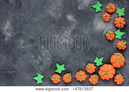 Halloween pumpkin background. Mini pumpkin candy frame on stone background top view with copy space