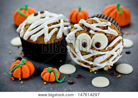 Halloween mummy cupcakes decorated with white chocolate on a stone table with sweet candy pumpkins selective focus