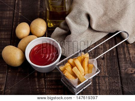 Fried french fries chips in fryer with ketchup on wood. with fresh potatoes and kitchen towel