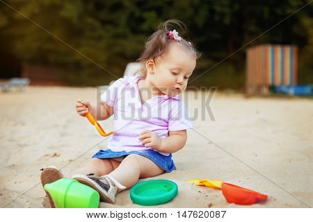 baby little girl playing in the sandbox toys. The concept of childhood and development.