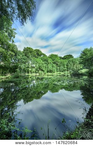 Landscape of a leafy green English countryside with a small water body in Cheshire England