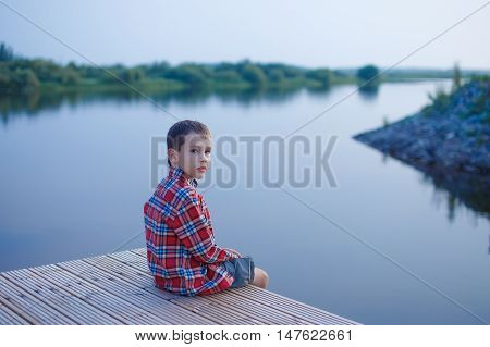 boy looks cautiously sitting near the water. child sitting on a wooden pier on the background of the river. quiet evening. boy startled looks back