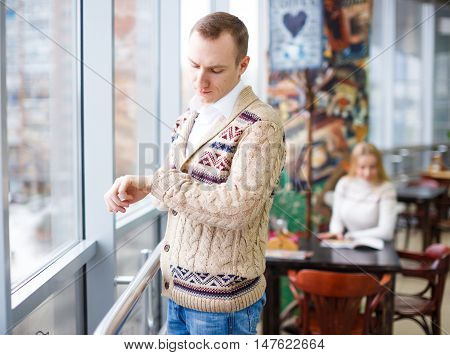 guy looks at the clock while waiting. young man standing at the window in a cafe waiting for his companion. in the background a beautiful young woman sitting at a table in a cafe and reading the menu