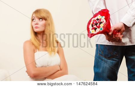 Man With Candy Bunch Flowers And Unhappy Woman.