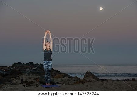 Landscape view of female athlete practicing Mountain Pose under full Harvest Moon.
