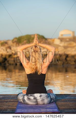 Athletic female seated on dock with hands in overhead Paryer Clasp while facing away.