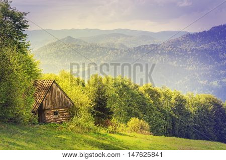 Spring mountain landscape in vintage style. Wooden hut in a clearing in the mountains.