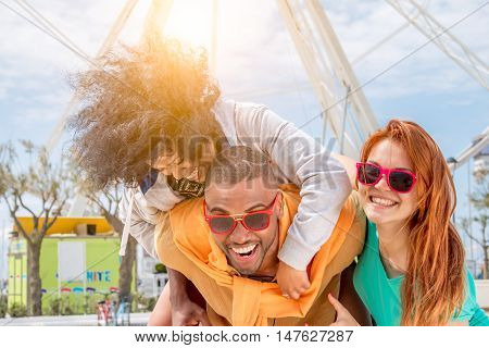 best friends with spontaneaous laughter - happy carefree friends of multi-ethinc origins having fun as black girl piggybacking on black guy and redhead blond girl is enjoying