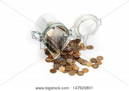 small coins and paper notes in a glass jar